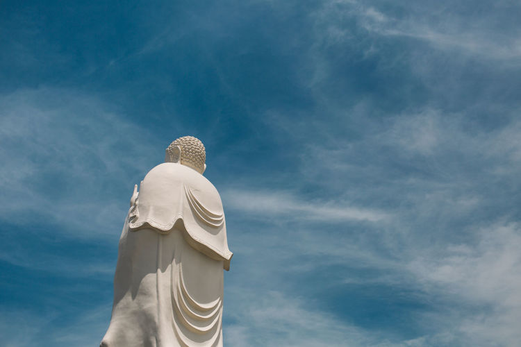 Low angle view of buddha statue against blue sky