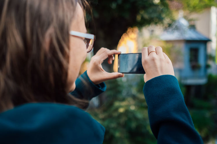 Woman photographing through mobile phone