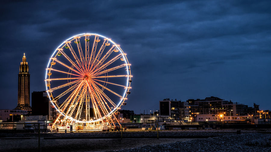 Illuminated Ferris Wheel Against Sky At Night