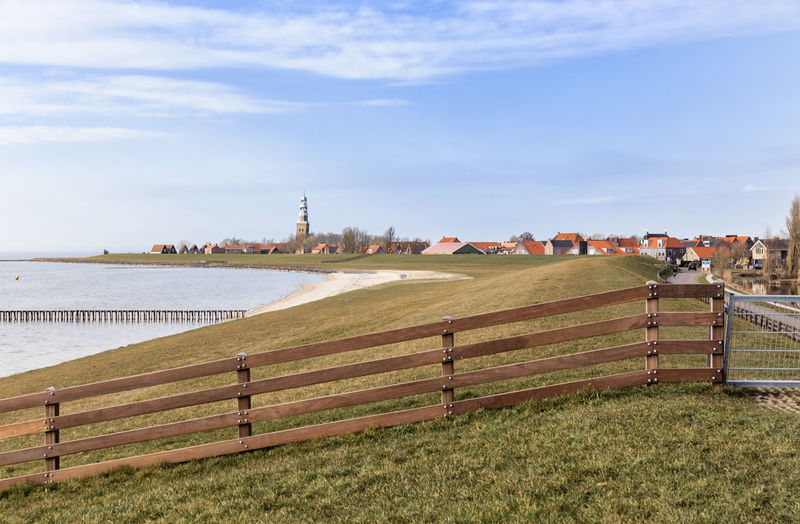 Dyke and townscape of Hindeloopen – Friesland, Netherlands, Europe Hindeloopen Friesland Netherlands Cityscape TOWNSCAPE Dyke  Fence Wood - Material Built Structure Building Exterior Water Lake Ijsselmeer Coastline No People Panorama Grass Landscape Barrier Railing Boundary Field Beauty In Nature Beach Village