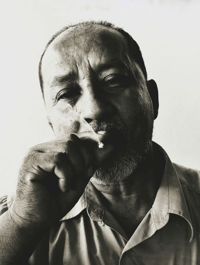Close-up portrait of mature man smoking against white background