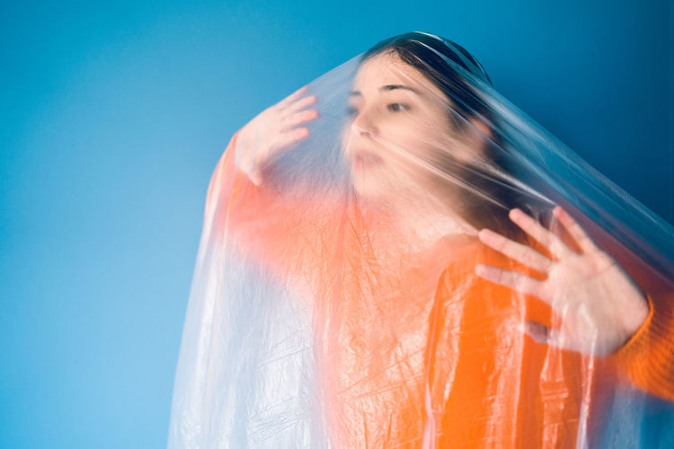 Woman covered in plastic standing against blue background