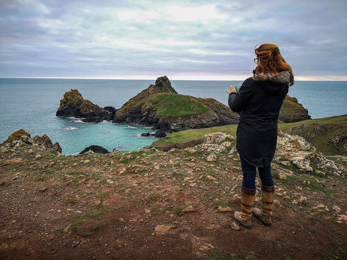woman exploring the lizard in Cornwall. taking pictures at kynance Getting Away From It All Away From The City EyeEm Nature Lover Water Sea Beach Standing Women Full Length Sand Wave Silhouette Calm Shore Horizon Over Water Idyllic Escapism Tranquil Scene Ocean Coastline Headland