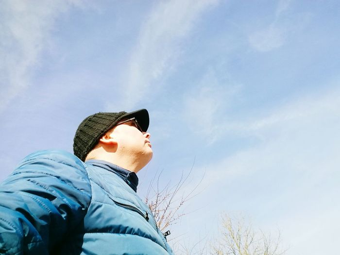 Low angle view of man in hat and sunglasses against sky during sunny day
