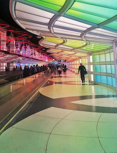 Colorful Abyss Flight Airport Walkway Colors Linear Perspective Photography Illuminated Men Women Water Architecture Built Structure Ceiling Ceiling Light  Recessed Light Hanging Light Light Fixture Hallway Interior Skylight Architecture And Art Passageway Large Group Of People
