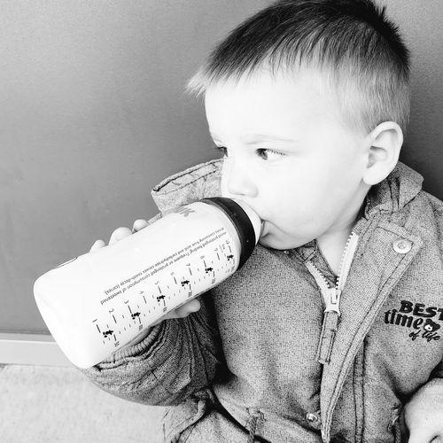 Close-up portrait of cute boy drinking