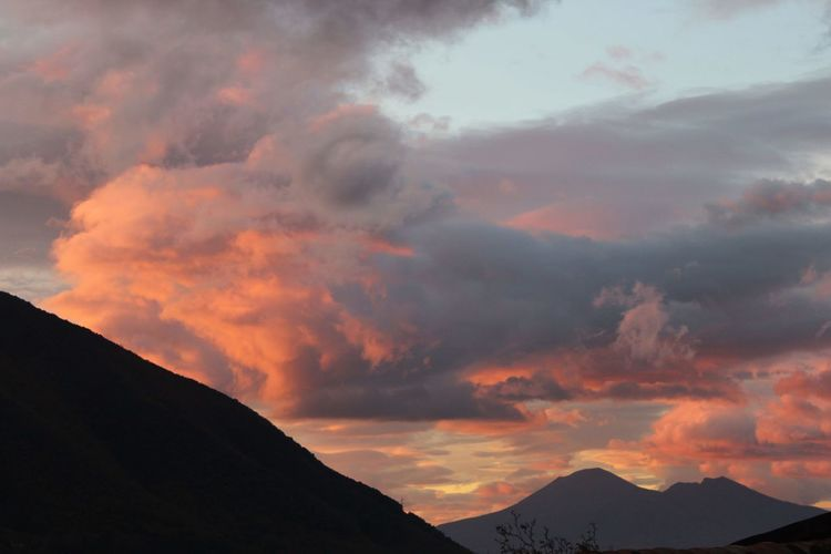 Low angle view of silhouette mountains against orange sky
