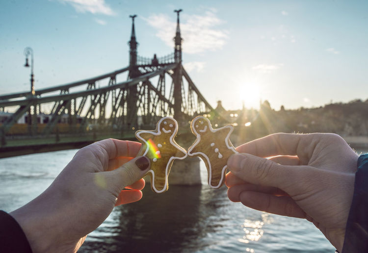 Cropped image of people holding gingerbread man against bridge