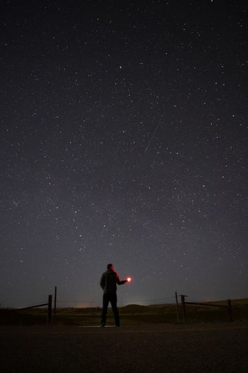 Full length of man standing on field against sky at night