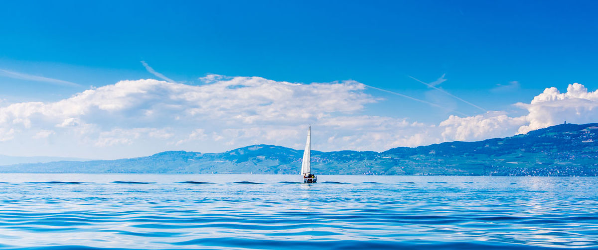 Boats in sea with mountains in background