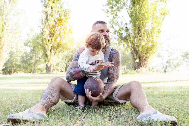 tattooed father have fun with his son in the park with rugby ball Men Family Togetherness Kid Child Happy Embrace Bearded Man Rugby Ball Tattoo Casual Clothing Day Love Bonding Positive Emotion Outdoors Park People Adorable Caucasian Plant Meadow Sitting Two People Real People Leisure Activity Grass Males  Childhood Emotion Nature Adult Son