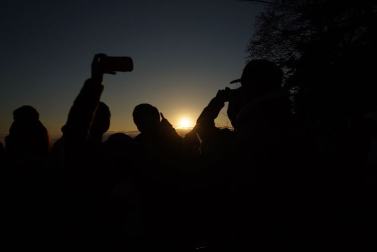Silhouette people photographing at sunset