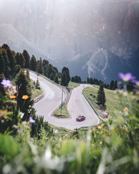 Transportation Mountain Road Plant Mode Of Transportation Tree Nature Car No People Motor Vehicle Land Vehicle Day High Angle View Beauty In Nature Outdoors City Sky Travel Mountain Range Scenics - Nature Flower Road Alpine Road Gröden Sella Pass