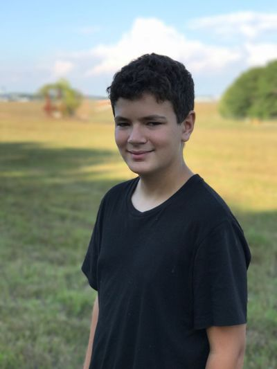 Portrait Of Teenage Boy Standing On Field