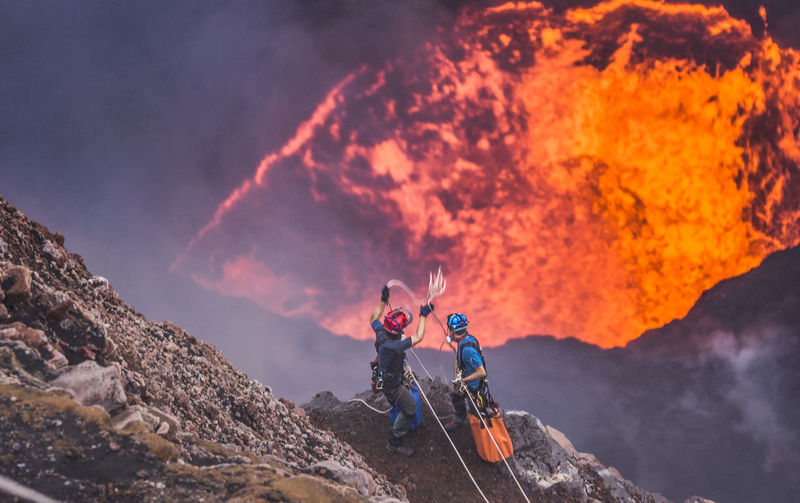 Man with fire on mountain against sky