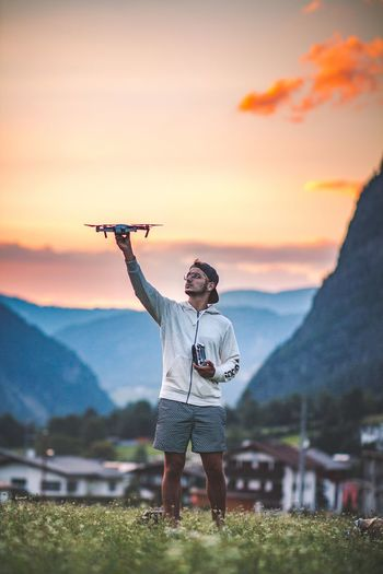 Man Holding Drone While Standing On Field Against Sky During Sunset