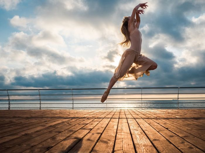 Young woman jumping on sea against sky