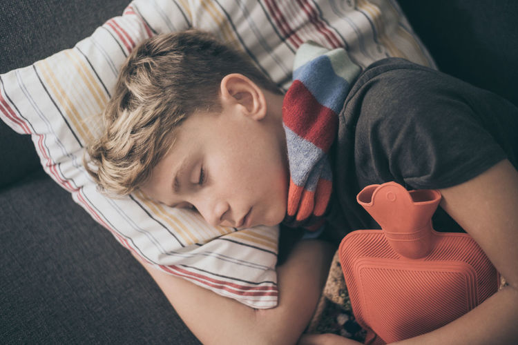 Directly above shot of ill boy sleeping on sofa at home