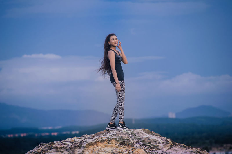 Portrait of young woman standing on rock against sky