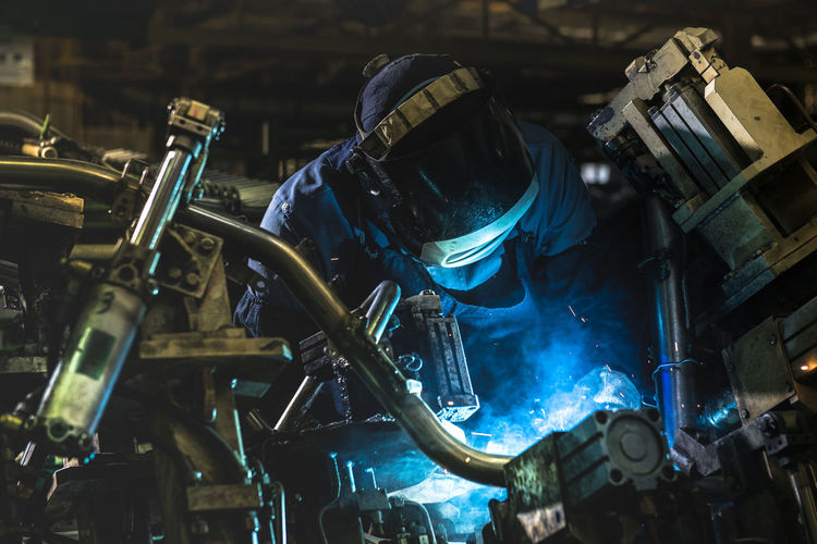Industrial workers are welding steel parts automotive.