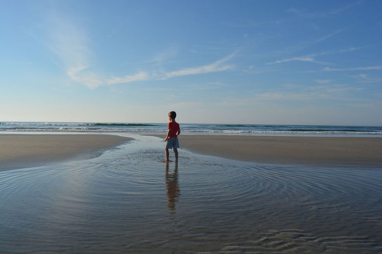 Full Length Rear View Of Boy Standing In Water At Beach Against Sky