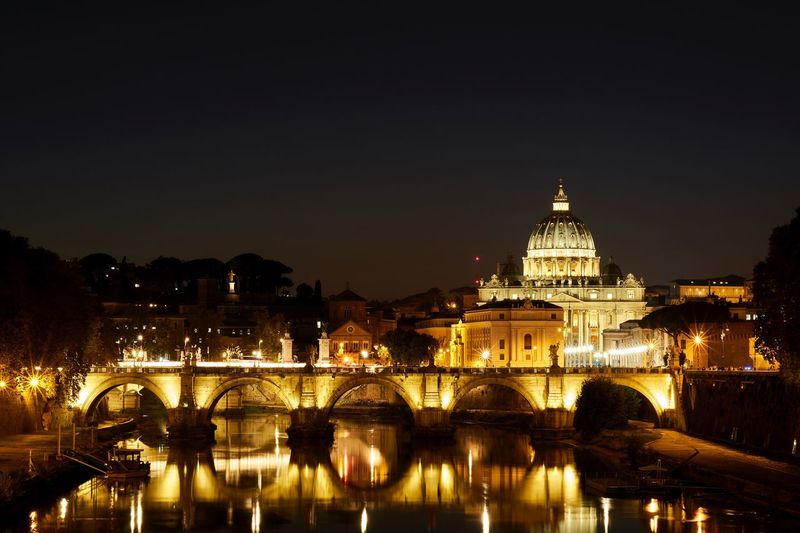 Illuminated arch bridge over tiber river in city at night