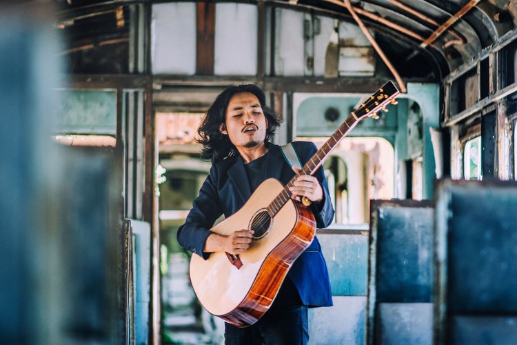 Young guitarist playing guitar in bus
