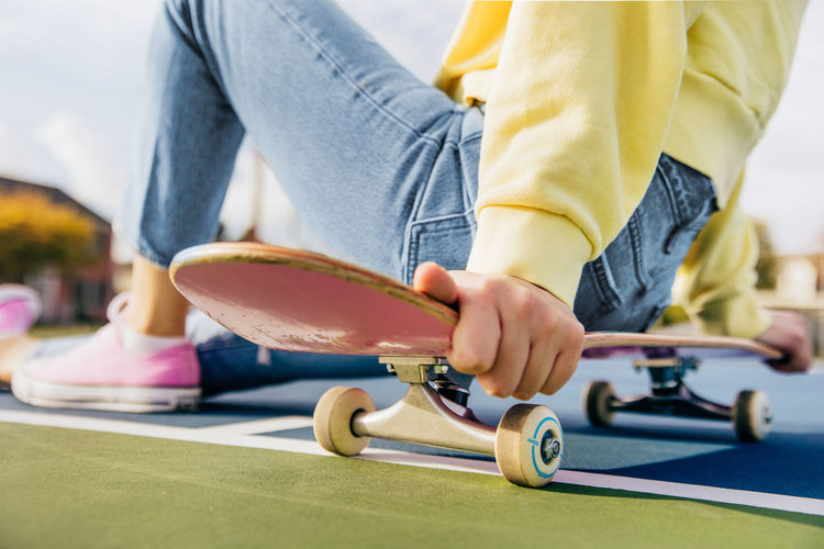 Close up of skateboard with girl sitting on it on a tennis court
