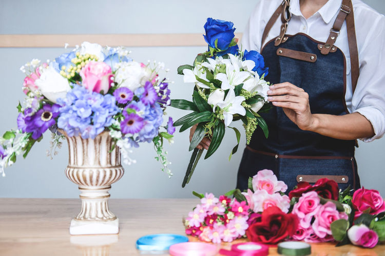 Midsection Of Man Arranging Flowers At Table