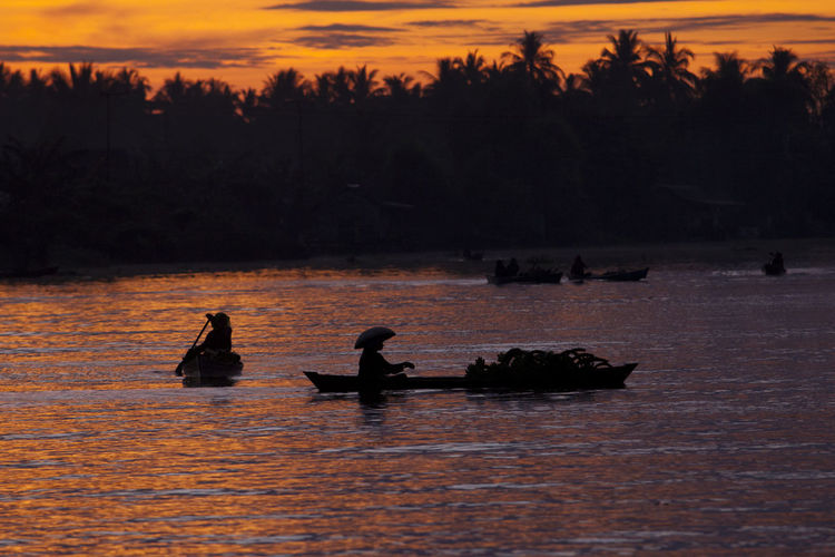 Silhouette people on boat in lake during sunset