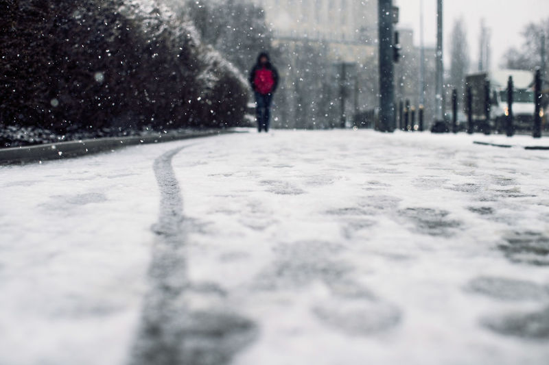 Surface level view of sidewalk during snowfall in city