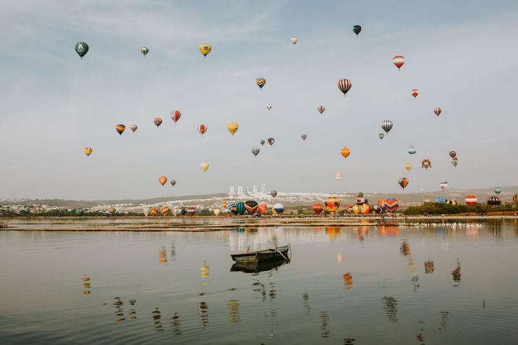 Hot air balloons flying over lake against sky