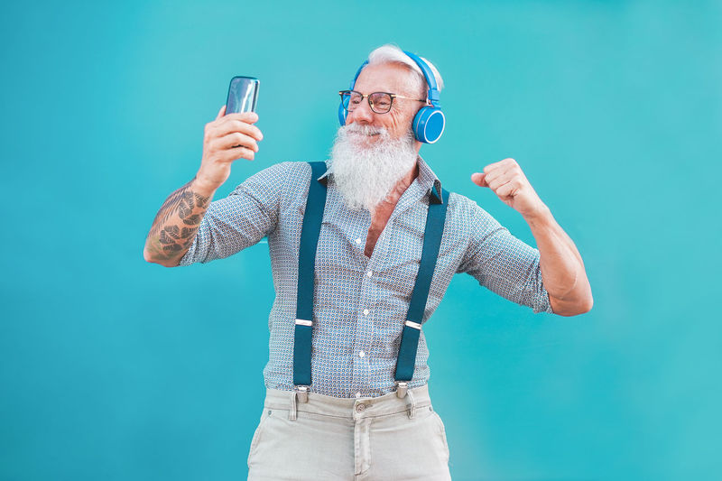 Senior hipster man using smartphone app for creating playlist music - Trendy tattoo guy having fun with mobile phone technology - Tech and joyful elderly lifestyle concept - Focus on his face Tattoo Senior Adult Phone Mobile Phone Music Playlist Fashion Trend One Person Beard Males  Men Adult Senior Men Eyeglasses  Mustache Mature Men Dancing Hipster Fit Man Listening