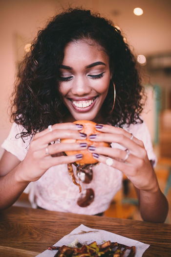 Smiling woman holding hamburger while sitting in cafe