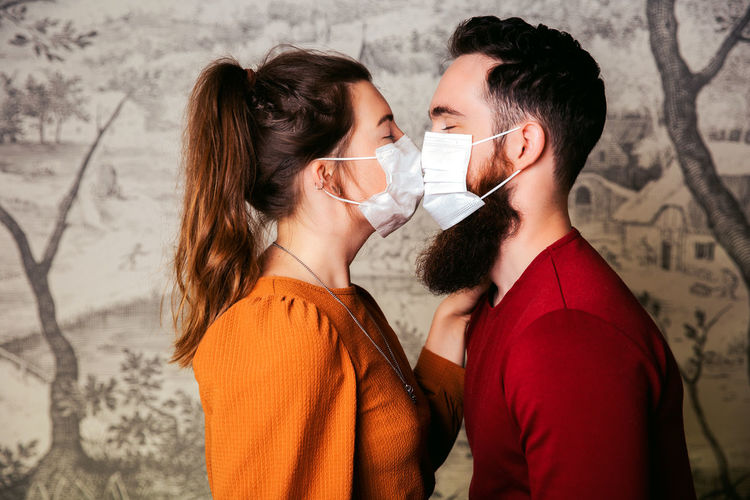 Side view of young couple wearing masks kissing against wall