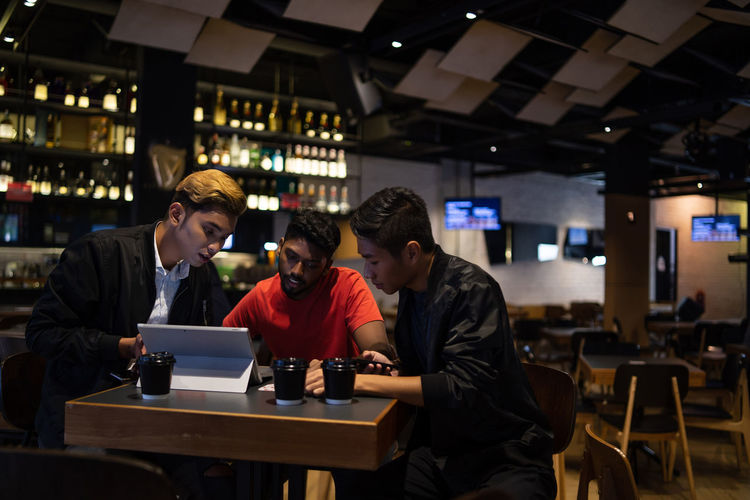 Friends using laptop while sitting in restaurant