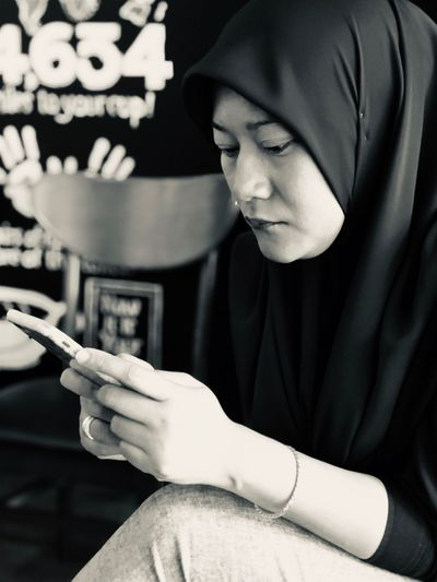 Mid Adult Woman Wearing Hijab Using Smart Phone While Sitting Indoors