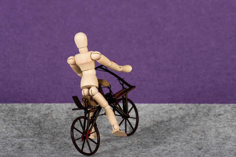 Wooden figurine on artificial bicycle against purple background