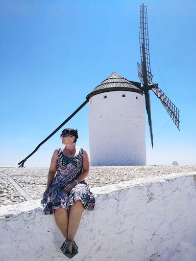 Woman wearing sunglasses while sitting on stone wall with traditional windmill in background