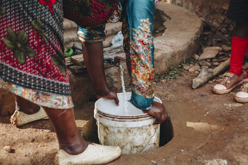 Africa African Child Clean Water Close-up Dirt Dirty Drinking Water Family Filling Filter Ground Health Low Section Outdoors PLASTIC CONTAINER Poor  Poverty Shoes Social Business Survival Tap Water Water Filter Women