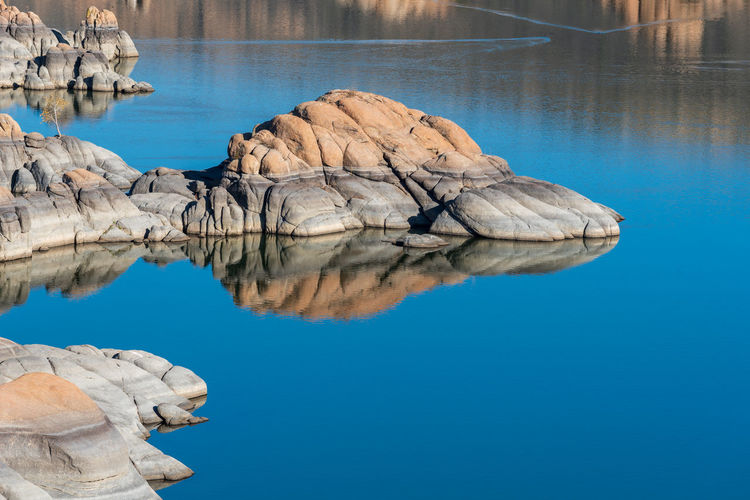 Two-toned rock formations, reflections and water at watson lake park in prescott, arizona