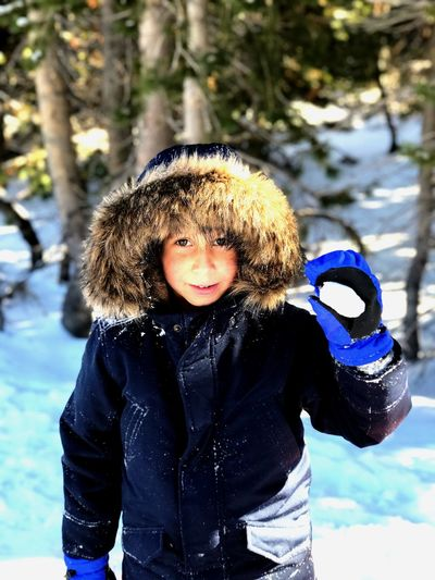 Portrait of boy standing on snow