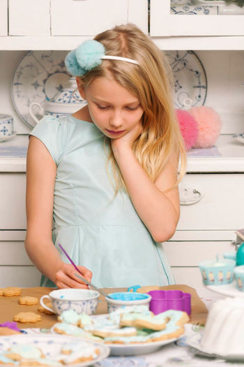 Girl making cookies at table in kitchen
