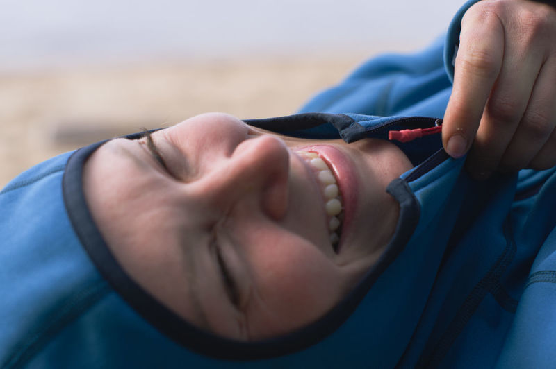 Portrait of a laughing woman in hooded fleece jacke by the shore. close-up