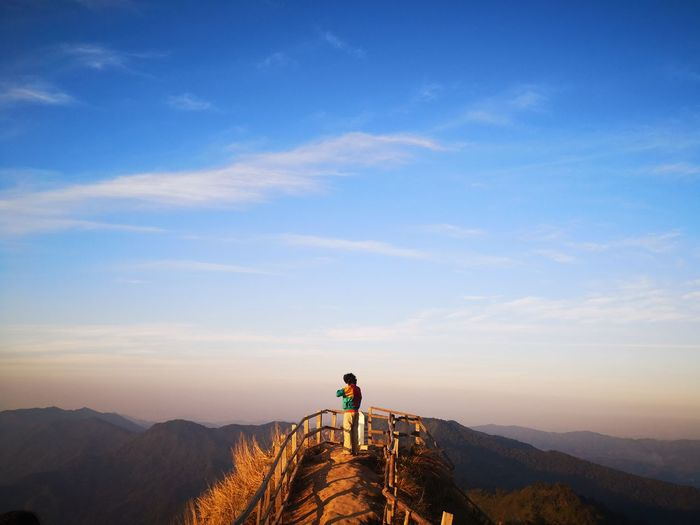 Woman standing at observation point against blue sky