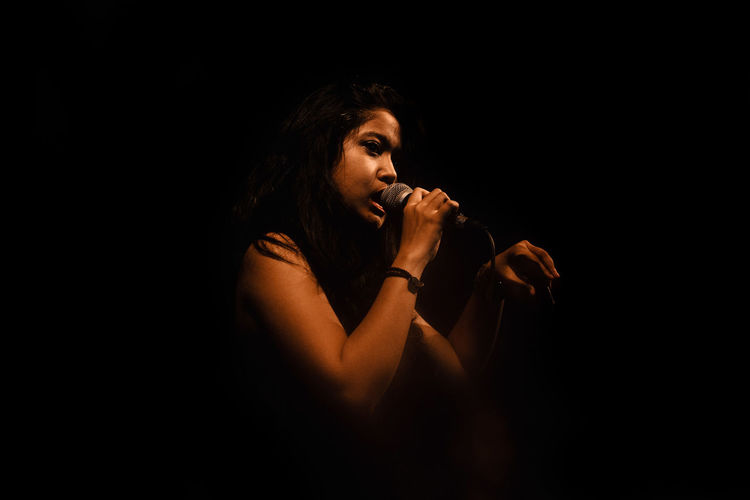 Side View Of Young Woman Singing On Microphone Against Black Background