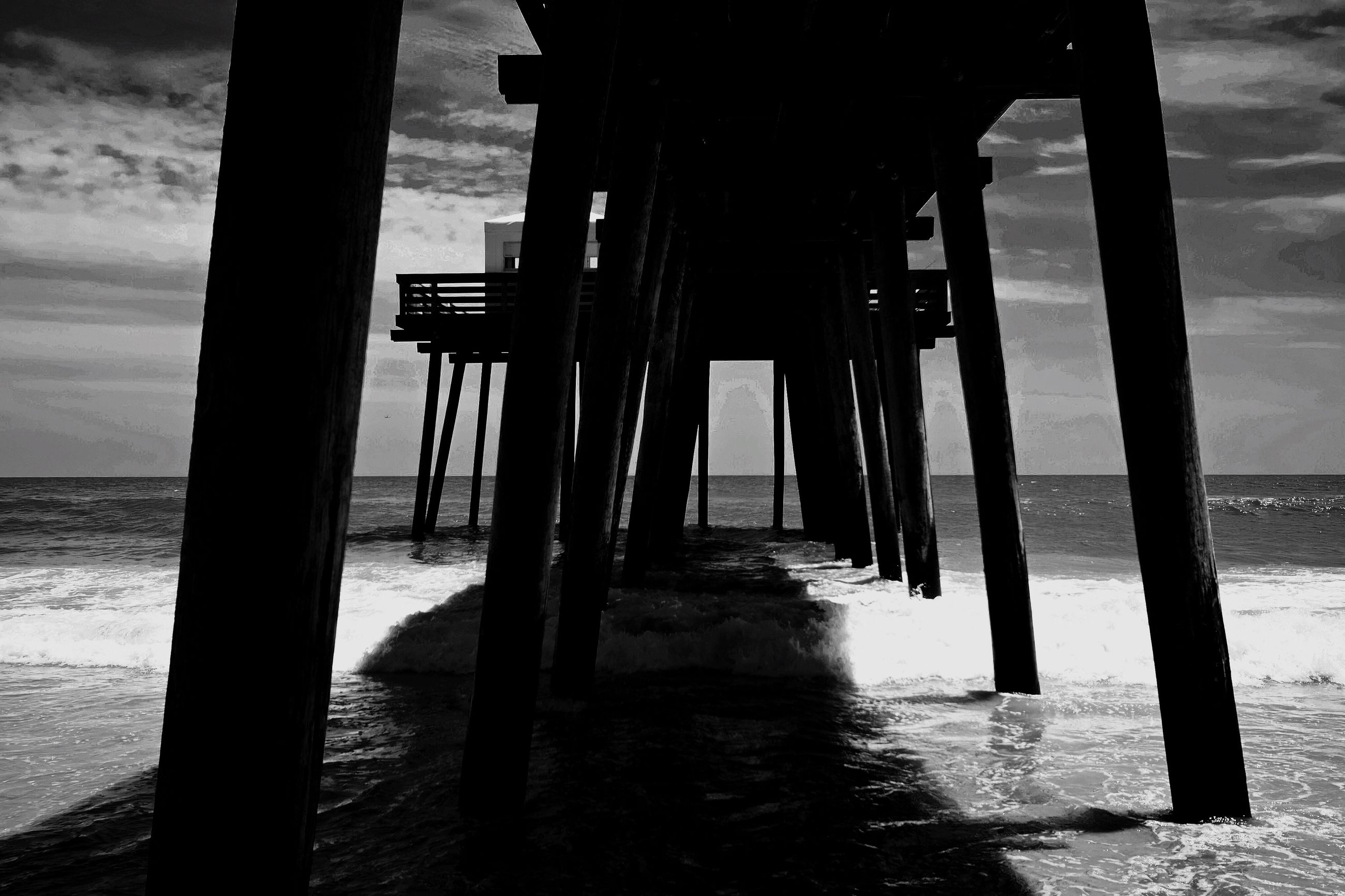 sea, water, pier, beach, horizon over water, built structure, column, in a row, support, architecture, shore, wave, surf, architectural column, vacations, scenics, tide, tranquil scene, sky, below, tranquility, pillar, supported, nature, outdoors, long, day, repetition, concrete, underneath, remote