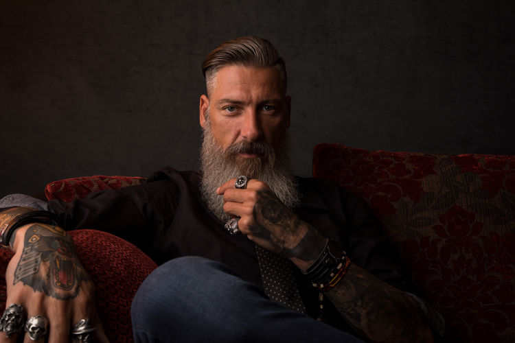 Portrait of an attractive modern business man in front of a dark background Couch Tattooed Beard Bearded Black Background Boss Businessman Casual Clothing Club Contemplation Jewlery Lifestyles Males  Manager Mature Adult Mature Men Men Millionaire Mustache One Person Portrait Rings Sitting Studio Shot Tattoo