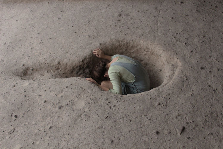 High angle view of girl sitting in hole