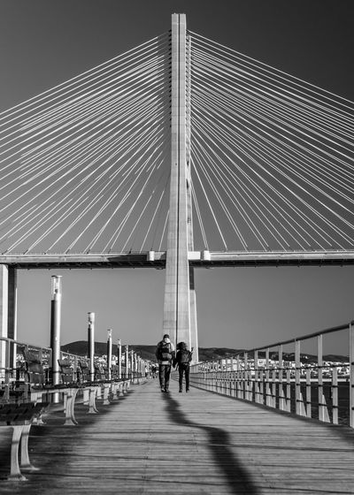 Portugal Architecture Blackandwhitephoto Bridge Bridge - Man Made Structure Built Structure Connection Day Lifestyles Men Outdoors People Portugal_lovers Real People Sky Suspension Bridge Togetherness Transportation Two People Vasco Da Gama Bridge Water Women